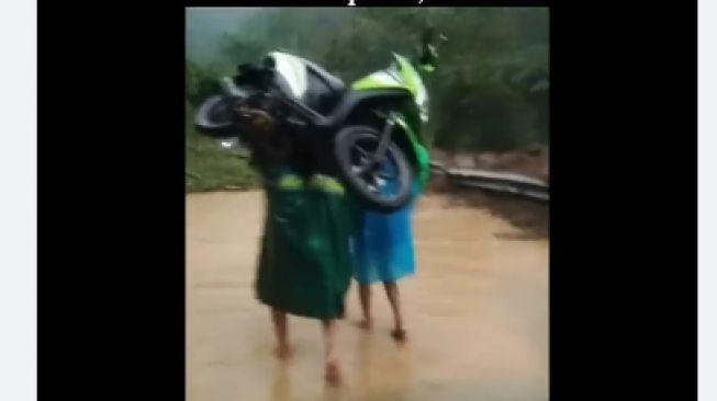 Pria Angkat Motor Matic Terobos Longsor di Malang